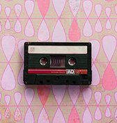 black cassette tape on top of a pink retro pattern
